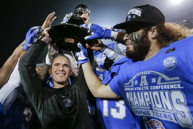 Memphis head coach Mike Norvell, left, celebrates with he team after they defeated Cincinnati in an NCAA college football game for the American Athletic Conference championship Saturday, Dec. 7, 2019, in Memphis, Tenn. (AP Photo/Mark Humphrey)