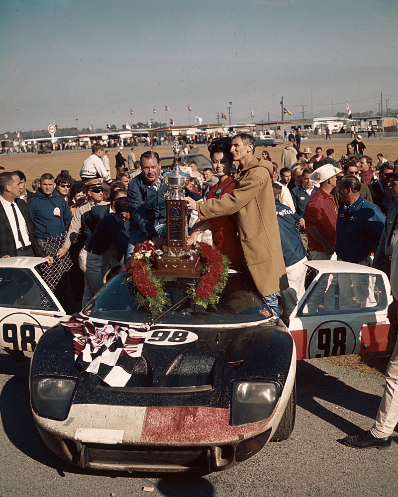 DAYTONA BEACH, FL — February 6, 1966: Lloyd Ruby (L) and Ken Miles (R) enjoy the spoils of victory lane after driving a Shelby American Ford MKII to victory in the 24 Hours of Daytona at Daytona International Speedway. The pair finished eight laps in front of their team car driven by Dan Gurney and Jerry Grant. (Photo by ISC Images & Archives via Getty Images)