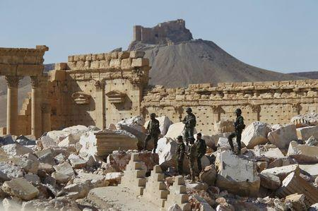 Syrian army soldiers stands on the ruins of the Temple of Bel in the historic city of Palmyra, in Homs Governorate, Syria in this April 1, 2016 file photo. The Fakhreddin's Castle is seen in the background. REUTERS/Omar Sanadiki/Files