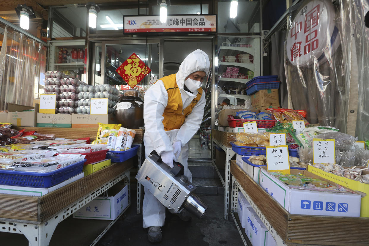 A worker wearing protective gears sprays disinfectant at a Chinese food store as a precaution against a new coronavirus at Daelim market in Seoul, South Korea, Wednesday, Feb. 5, 2020. Deaths from a new virus rose to 490 in mainland China on Wednesday while new cases on a Japanese cruise ship, in Hong Kong and in other places showed the increasing spread of the outbreak and renewed attention toward containing it. (AP Photo/Ahn Young-joon)