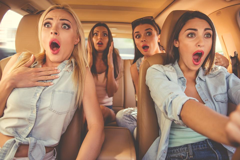 Young women sitting with open mouths in a car.
