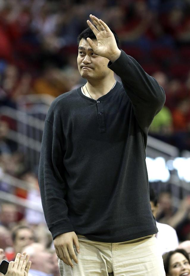 Former Houston Rockets Yao Ming waves to the crowd in the first half of an NBA basketball game between the Rockets and the Denver Nuggets Saturday, Nov. 16, 2013, in Houston. (AP Photo/Pat Sullivan)