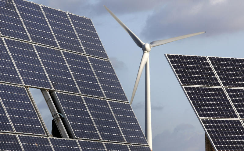 """FILE - In this Nov. 30, 2011 file photo photovoltaic modules and a windmill of the wind farm are pictured at the village of Feldheim near Berlin, Germany. The crisis in Ukraine is underlining the urgency of Germany's biggest political challenge as Chancellor Angela Merkel's new government marks 100 days in office Wednesday, March 26, 2014, getting the country's mammoth transition from nuclear to renewable energy sources on track. The transition started in earnest when Merkel, after Japan's 2011 Fukushima nuclear disaster, abruptly accelerated Germany's exit from nuclear power. Since then, the """"Energiewende"""" _ roughly, """"energy turnaround"""" _ has created increasing headaches. (AP Photo/Michael Sohn, File)"""