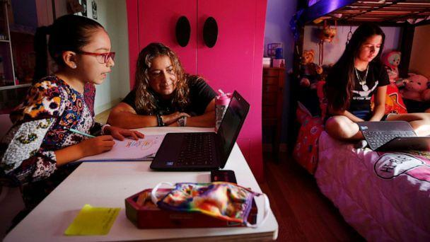 PHOTO: In this Sept. 17, 2020 file photo, children in Los Angeles use laptop computers during remote learning classes at home while their mom assists them. (Al Seib/Los Angeles Times via Getty Images, FILE)