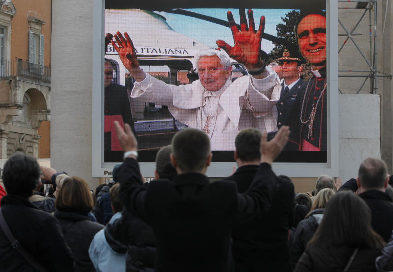 Faithful watch a giant screen showing Pope Benedict XVI  in St. Peter's Square, at the Vatican,Thursday, Feb. 28, 2013. The 85-year-old German Pope Benedict is stepping down on Thursday evening, the first pope to do so in 600 years, after saying he no longer has the mental or physical strength to vigorously lead the world's 1.2 billion Catholics. (AP Photo/Dmitry Lovetsky)