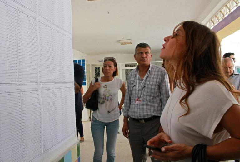 Salwa Smaoui, wife of jailed Tunisian presidential candidate Nabil Karoui, looks for her name before casting her ballot on Sunday