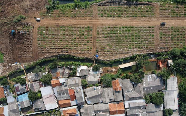An aerial view of a graveyard for Covid victims at Srengseng Sawah cemetery in Jakarta, a day before the implementation of emergency restrictions - BAY ISMOYO/AFP
