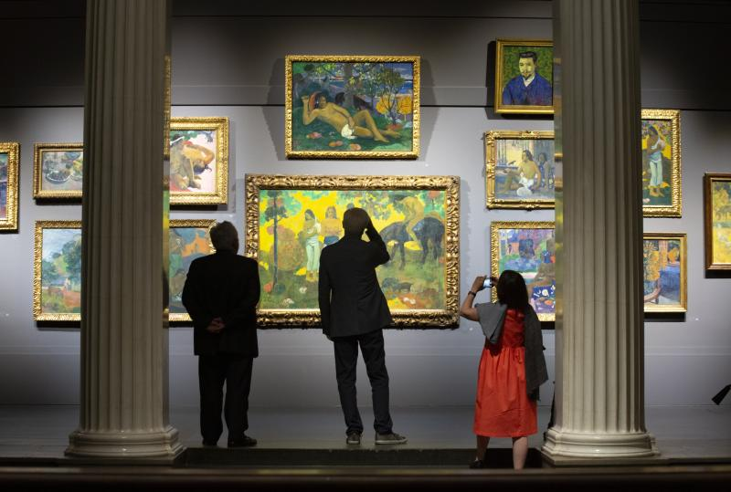 Visitors look at painting by Paul Gauguin and Vincent van Gogh of the collections of Sergei Shchukin, one of the most prominent collections of European Modernist art, encompassing the most important artistic trends of the late 19th and early 20th centuries at The Pushkin State Museum of Fine Arts in Moscow, Russia, Tuesday, June 18, 2019. The exhibition will include masterpieces by Claude Monet, Pierre Auguste Renoir, Paul Cezanne, Paul Gaugin, Vincent van Gogh, Henri Matisse, Pablo Picasso, and other masters. (AP Photo/Alexander Zemlianichenko)