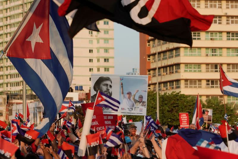 FILE PHOTO: People carry a poster with photographs of Fidel Castro, Miguel Diaz-Canel and Raul Castro during a rally in Havana