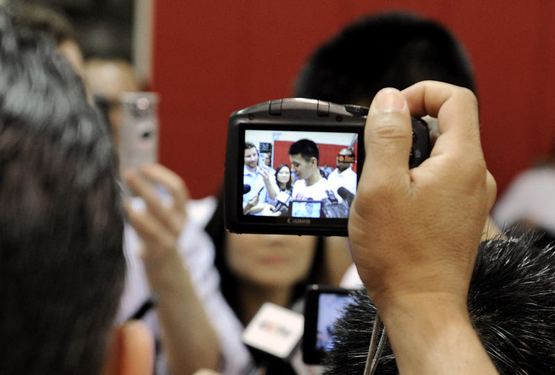A journalist holds up a camera to photograph Houston Rockets' Jeremy Lin as Lin speaks with the media after NBA basketball practice, Tuesday, Sept. 18, 2012, in Houston. (AP Photo/Pat Sullivan)