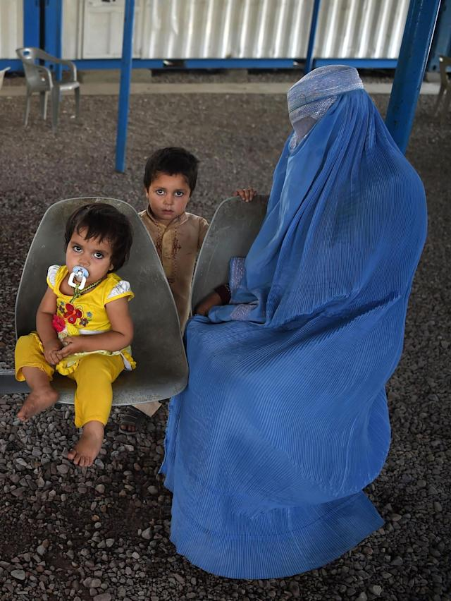 <p>An Afghan refugee woman sits with her children at the registration center of United Nations High Commissioner for Refugees (UNHCR) in the Pakistani city of Peshawar on June 19, 2017 ahead of the World Refugee Day. A record 370,000 Afghans left Pakistan last year, many of whom were second or even third generation migrants of people fleeing the Soviet invasion of Afghanistan during the 1980s, surging from 55,000 the year before. (Photo: Abdul Majeed /AFP/Getty Images) </p>