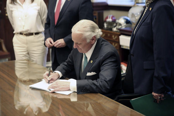 South Carolina Gov. Henry McMaster signs a bill requiring schools to provide in-person classes five days a week starting April 26 and for next school year on Thursday, April 22, 2021, in Columbia, S.C. The bill also requires school districts to pay teachers extra if they have to teach both in person and online. (AP Photo/Jeffrey Collins)