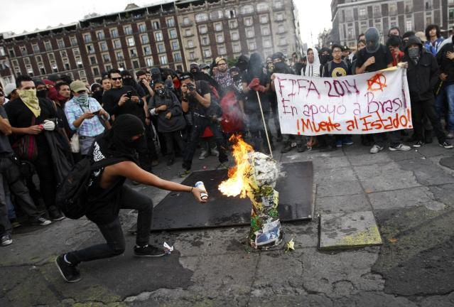 "An anarchist protester sets a mock World Cup trophy on fire during a march in Mexico City June 10, 2014. Anarchists staged a protest against the World Cup during a march in commemoration of the 43rd anniversary of the Halconazo, when a Mexican paramilitary unit called the Halcones (Falcons) killed an unknown number of students during a demonstration in 1971. The sign in the back reads ""FIFA 2014, in support of Brazil, death to the state."" REUTERS/Bernardo Montoya (MEXICO - Tags: POLITICS CIVIL UNREST SPORT SOCCER WORLD CUP)"