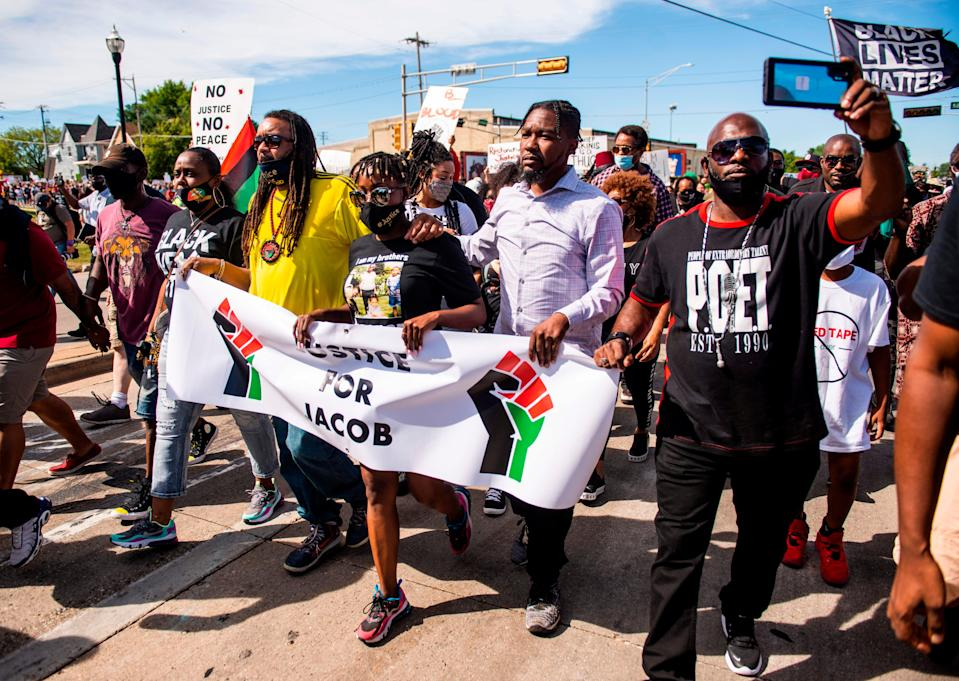 justin blake, letetra wideman, and supporters march holding a sign that says justice for jacob