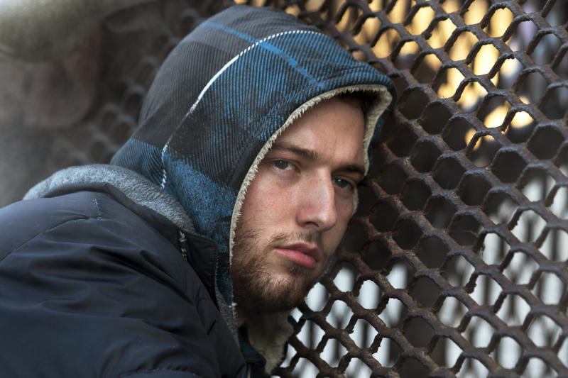 Nicholas Simmons, 20, of Greece, N.Y., warms himself on a steam grate with three homeless men by the Federal Trade Commission, just blocks from the Capitol, during frigid temperatures in Washington, Saturday, Jan. 4, 2014. On New Year's Day, Simmons disappeared from his parents' house in a small upstate New York town, leaving behind his wallet, cellphone and everything else. Four days later, an Associated Press photographer, looking for a way to illustrate unusually cold weather, took his picture as he warmed himself on a steam grate a few blocks from the U.S. Capitol. His parents Paul and Michelle Simmons saw the photograph in USA Today Sunday morning after it was brought to their attention through a Facebook page set up to help find their son, according to police and family friends, and were able to report his location to D.C. police who transported him to a hospital where he was reunited with his father and brother who drove all day to find him. (AP Photo/Jacquelyn Martin)