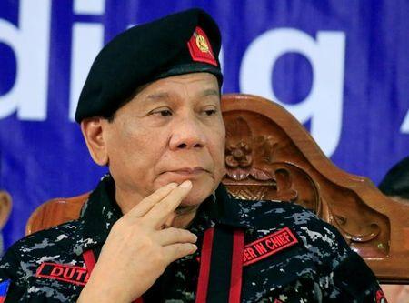 Philippine President Rodrigo Duterte, wearing a military uniform, gestures as he attends the 67th founding anniversary of the First Scout Ranger regiment in San Miguel town, Bulacan province, north of Manila