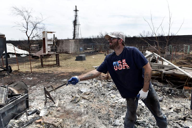 Johnny Lynes sifts through the remains of his parents home that was destroyed by the Rhea Fire near Taloga, Oklahoma.