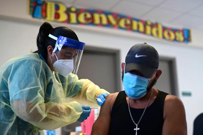 A healthcare worker is pictured injecting a man with a Moderna COVID-19 vaccine dose during a mass vaccination campaign at María Simmons School in Vieques, Puerto Rico.