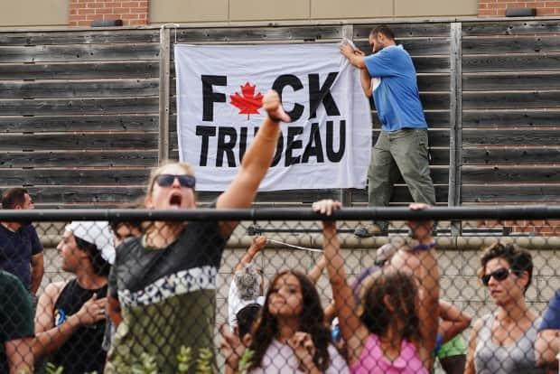 Protesters wait for Liberal Leader Justin Trudeau to arrive at a campaign event in Bolton, Ont., on Friday. The angry crowds outnumbered police and the event had to be cancelled. Another protest in Cambridge, Ont., today was delayed for an hour after crowds protesting against Trudeau hurled death threats, anti-lockdown and vaccine comments and racial and sexist slurs.  (Sean Kilpatrick/The Canadian Press - image credit)