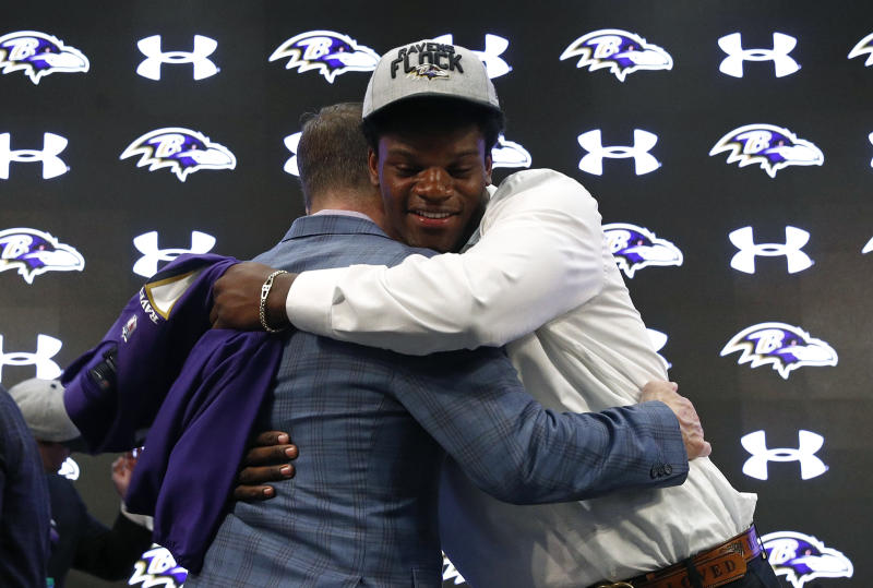 Quarterback Lamar Jackson, right, hugs Ravens coach John Harbaugh. (AP)