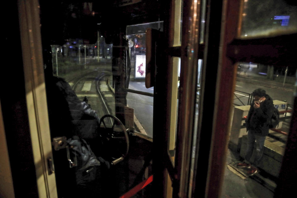 A man who stepped off a tram streetcar, right, waits at a stop as the tram moves on, in Milan, northern Italy, Sunday, Oct. 25, 2020. Since the 11 p.m.-5 a.m. curfew took effect last Thursday, people can only move around during those hours for reasons of work, health or necessity. (AP Photo/Luca Bruno)