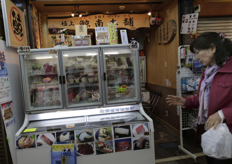 A shopper walks past a whale meat specialty store at Tokyo's Ameyoko shopping district, Thursday, March 27, 2014. The greatest threat to Japan's whaling industry may not be the environmentalists harassing its ships or the countries demanding its abolishment, but Japanese consumers. They've simply lost their appetite. The amount of whale meat stockpiled for lack of buyers has nearly doubled over 10 years, even as anti-whaling protests helped drive catches to record lows. More than 2,300 mink whales worth of meat is sitting in freezers while whalers still plan to catch another 1,300 whales per year. Uncertainty looms ahead of an International Court of Justice ruling expected Monday over a 2010 suit filed by Australia, which argues that Japan's whaling - ostensibly for research - is a cover for commercial hunts. (AP Photo/Shizuo Kambayashi)