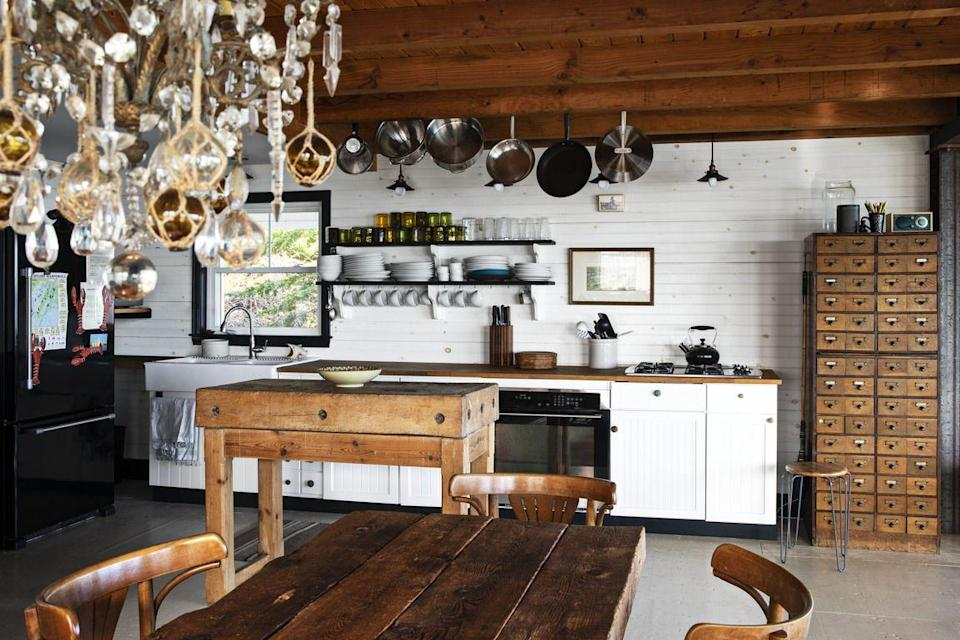 <p>Painted floors (Farrow and Ball's Wood Floor Primer & Undercoat in Old White) makes for a suitable companion to the patinaed pieces in this coastal Maine cottage. Horizontal wood paneling on the walls and lower cabinets keep a possibly dark space light and bright.</p>