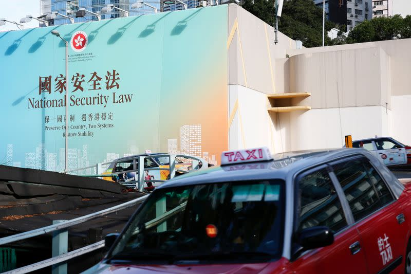 Taxis drive past government-sponsored advertisement promoting the new national security law during a meeting on national security legislation, in Hong Kong