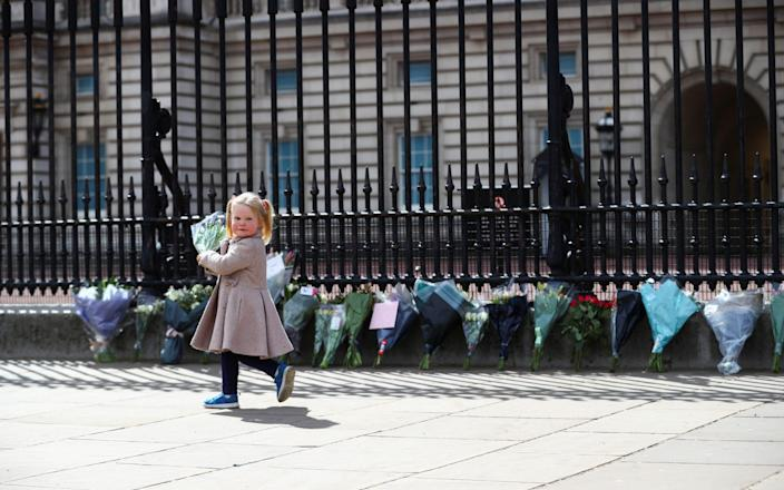 Maggie, 2, puts a bouquet outside Buckingham Palace after it was announced that Queen Elizabeth's husband, Prince Phillip of England, had died at the age of 99-Hanna McKay / Reuters & # xa0;