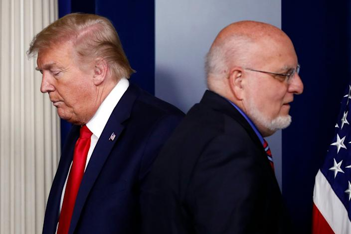 In this April 22, 2020, file photo President Donald Trump passes Dr. Robert Redfield, director of the Centers for Disease Control and Prevention, during a briefing about the coronavirus in the James Brady Press Briefing Room of the White House in Washington.