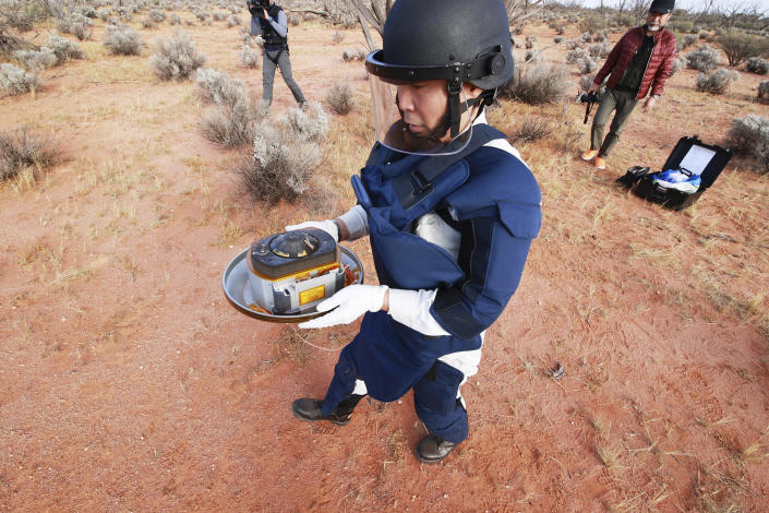 In this photo provided by the Japan Aerospace Exploration Agency (JAXA), a member of JAXA retrieves a capsule dropped by Hayabusa2 in Woomera, southern Australia, Sunday, Dec. 6, 2020. A Japanese capsule carrying the first samples of asteroid subsurface shot across the night atmosphere early Sunday before successfully landing in the remote Australian Outback, completing a mission to provide clues to the origin of the solar system and life on Earth. (JAXA via AP)
