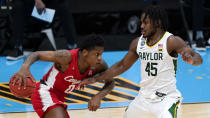 Houston guard Marcus Sasser (0) drives past Baylor guard Davion Mitchell (45) during the first half of a men's Final Four NCAA college basketball tournament semifinal game, Saturday, April 3, 2021, at Lucas Oil Stadium in Indianapolis. (AP Photo/Michael Conroy)