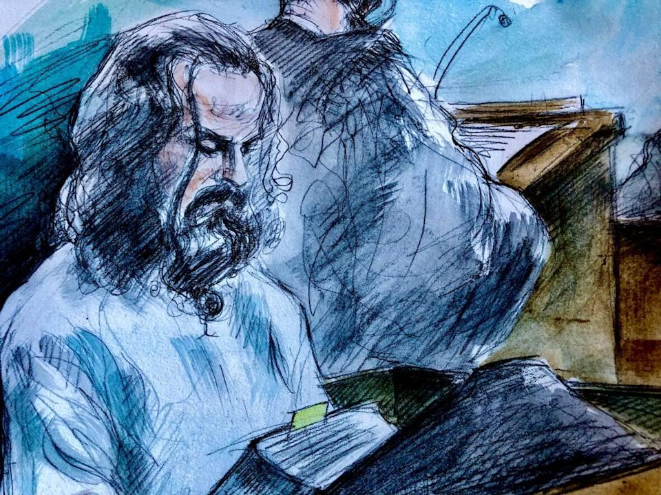 Cory Fenn, who is accused of killing a woman and her two children in 2018, holds a dictionary in the prisoner's box at the Superior Court of Justice in Oshawa during his trial. (Pam Davies/CBC - image credit)