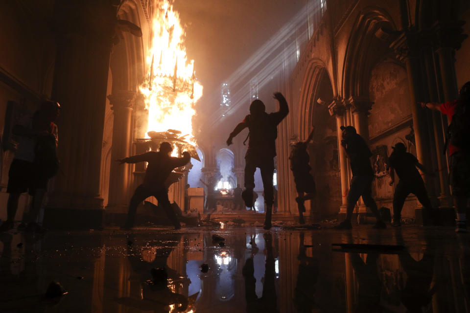 Protesters storm the San Francisco de Borja church, that belongs to Carabineros, Chile's national police force, on the one-year anniversary of the start of anti-government mass protests over inequality in Santiago, Chile, Sunday, Oct. 18, 2020.  (AP Photo/Esteban Felix)