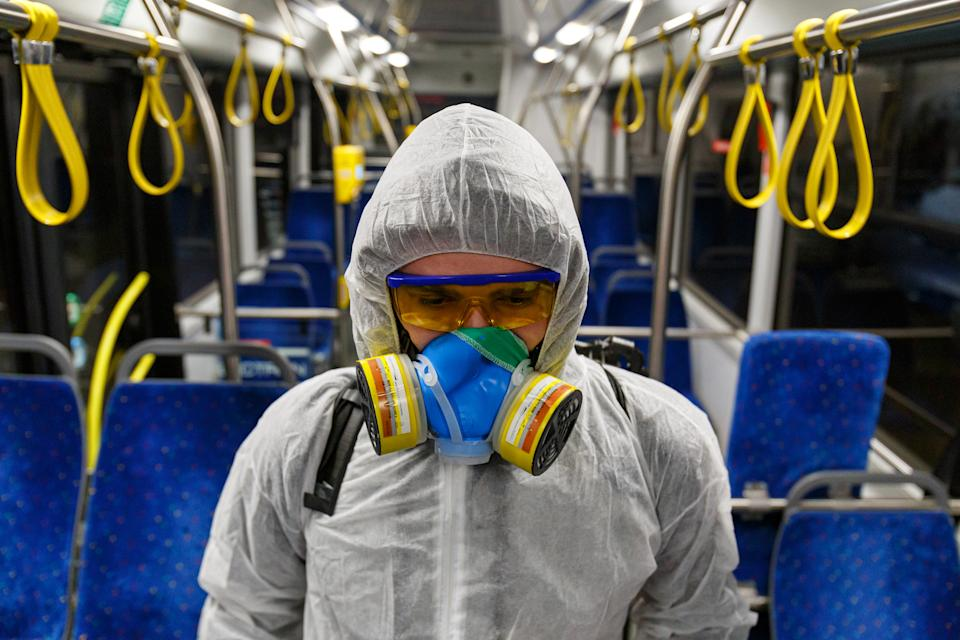 A person wears PPE equipment on public transport.