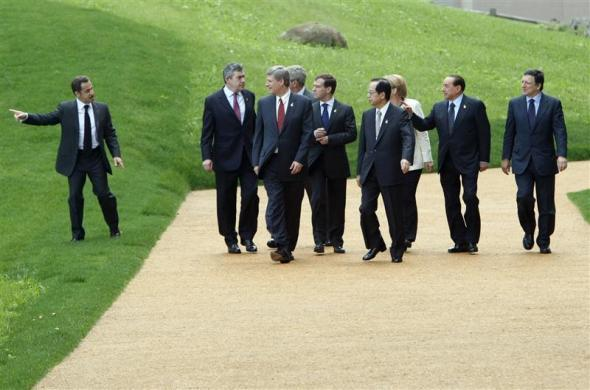 Group of Eight (G8) leaders head for a group photo session as French President Nicolas Sarkozy gestures at the G8 Hokkaido Toyako Summit in Toyako July 8, 2008. They are (L-R): Sarkozy, British Prime Minister Gordon Brown, Canada's Prime Minister Stephen Harper, U.S. President George W. Bush, Russia's President Dmitry Medvedev, Japan's Prime Minister Yasuo Fukuda, German Chancellor Angela Merkel, Italy's Prime Minister Silvio Berlusconi and European Commission President Jose Manuel Barroso.
