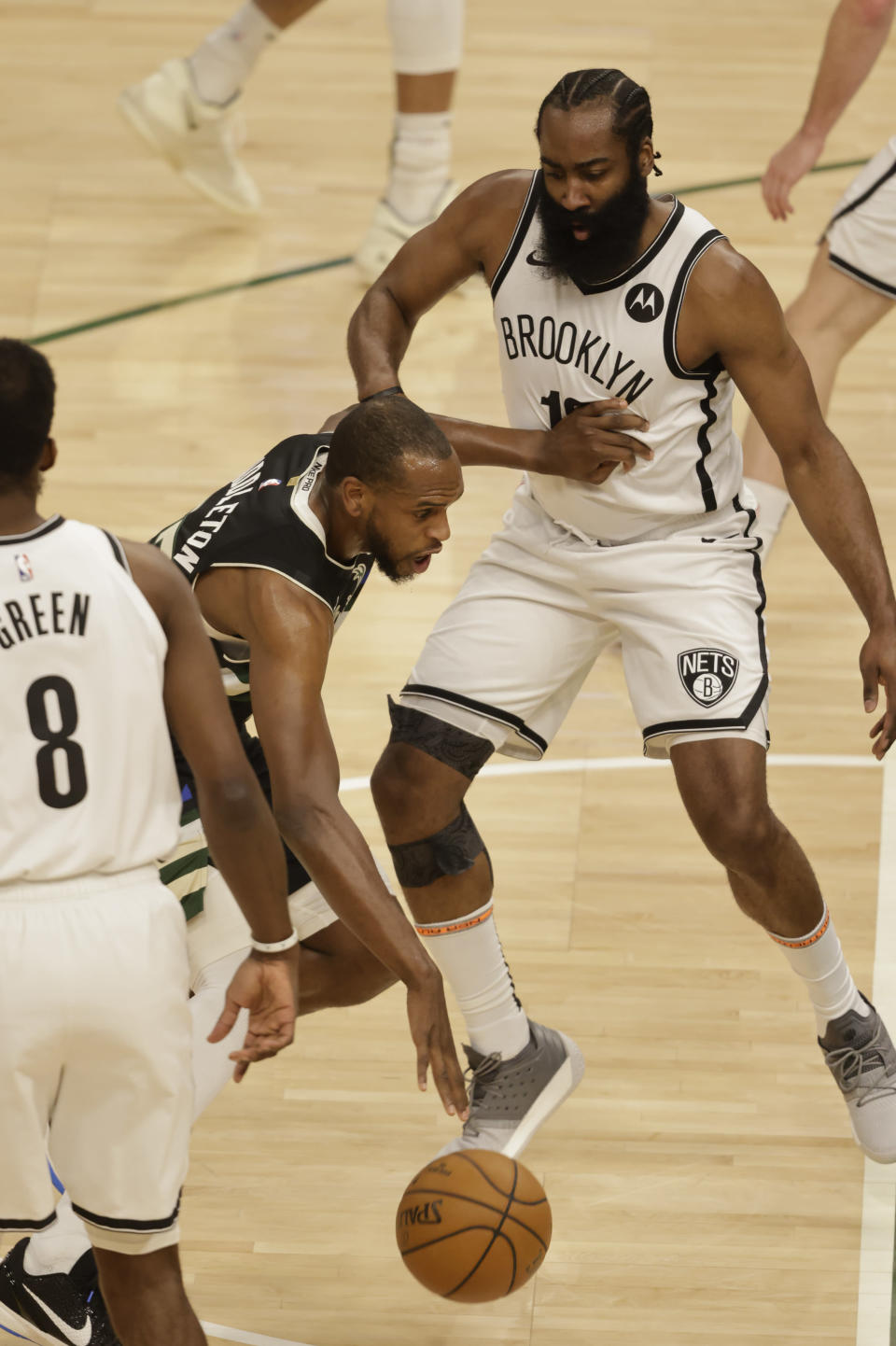 Milwaukee Bucks forward Khris Middleton, center, drives against Brooklyn Nets guard James Harden, right, during the first half of Game 6 of a second-round NBA basketball playoff series Thursday, June 17, 2021, in Milwaukee. (AP Photo/Jeffrey Phelps)