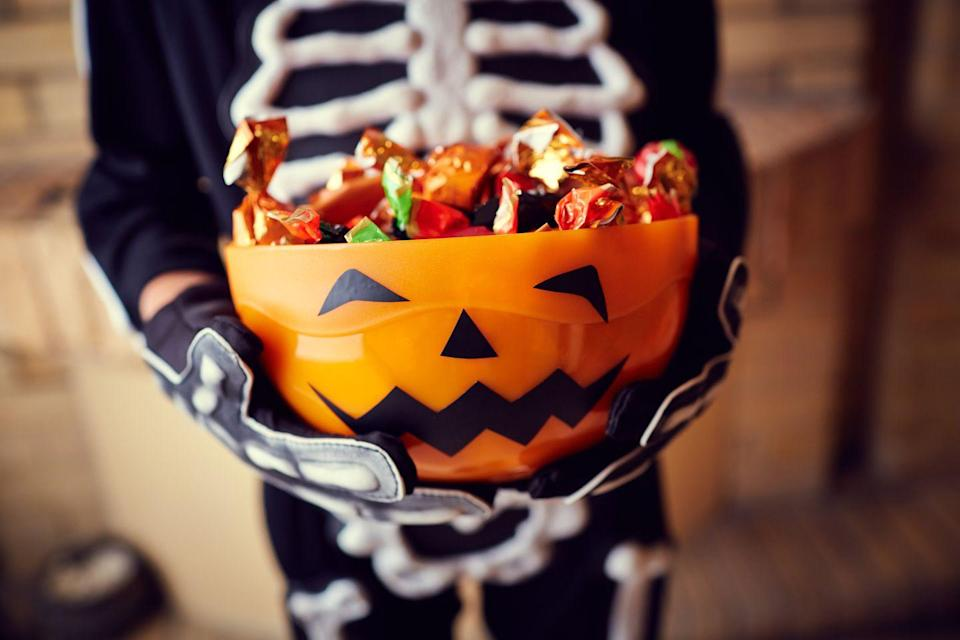 """<p>Grab a bucket of relatively flat <a href=""""https://www.goodhousekeeping.com/holidays/halloween-ideas/news/a40935/buy-the-cheapest-halloween-candy/"""" rel=""""nofollow noopener"""" target=""""_blank"""" data-ylk=""""slk:Halloween candies"""" class=""""link rapid-noclick-resp"""">Halloween candies</a> (think Kit-Kat or Hershey's bars) and take turns stacking them on top of one another. The first person to knock down the stack loses — and the winners get to split the sweet loot. </p>"""