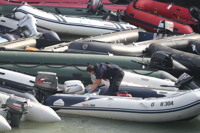 A Border Force officer attends to a collection of ribs and dinghys, thought to have been used in small boat incidents in the English Channel (Gareth Fuller/PA)