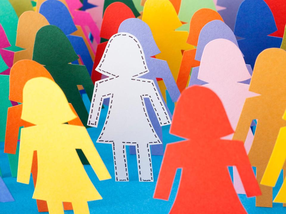Female sticker figures in multiple colors standing while white stick figure is centered.