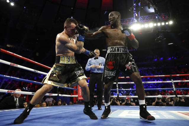 Terence Crawford, right, punches Lithuania's Egidijus Kavaliauskas, knocking him down for a TKO in the ninth round of a WBO welterweight boxing match, Saturday, Dec. 14, 2019, in New York. (AP Photo/Michael Owens)