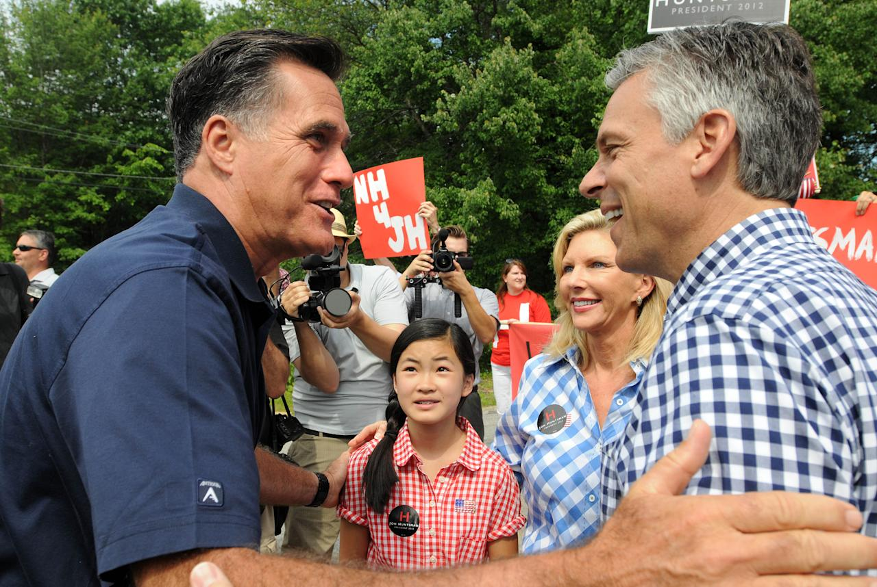AMHERST, NH - JULY 4: Republican presidential candidates Former Ambassador to China Jon Huntsman (R) and former Massachusetts governor Mitt Romney (L) greet to each other prior to marching in a Fourth of July parade as Huntsman's wife Mary Kaye (2nd R) and daughter Gracie Mei look on July 4, 2011 in Amherst, New Hampshire. Romney, considered the republican front runner,  raised nearly 20 million in the second quarter. (Photo by Darren McCollester/Getty Images)
