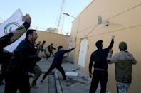 Iraqi protesters tear a security camera off a wall at the US embassy compound in Baghdad