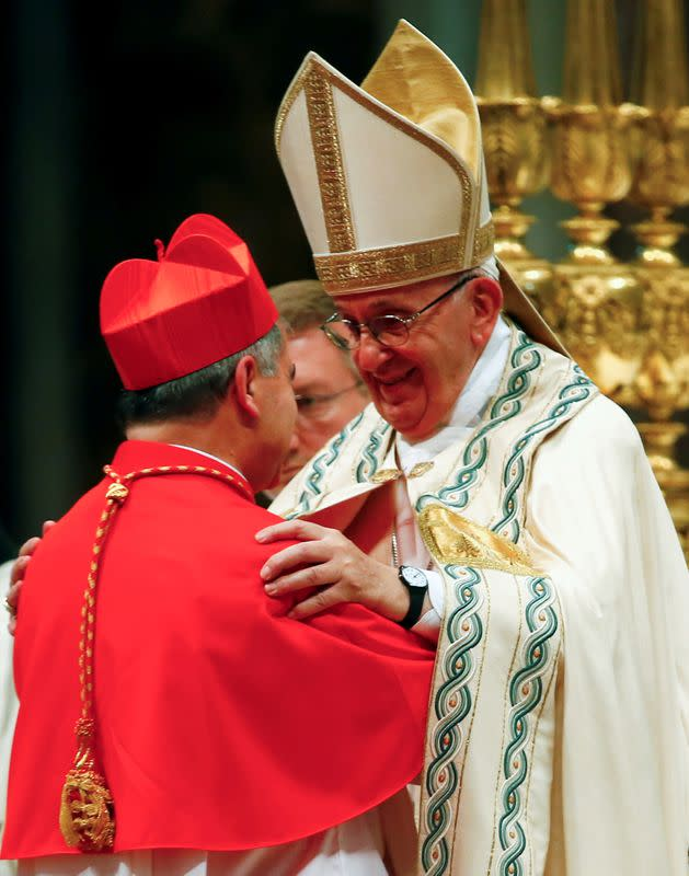 FILE PHOTO: Pope Francis blesses new cardinal Giovanni Angelo Becciu of Italy during a consistory ceremony to install 14 new cardinals in Saint Peter's Basilica at the Vatican