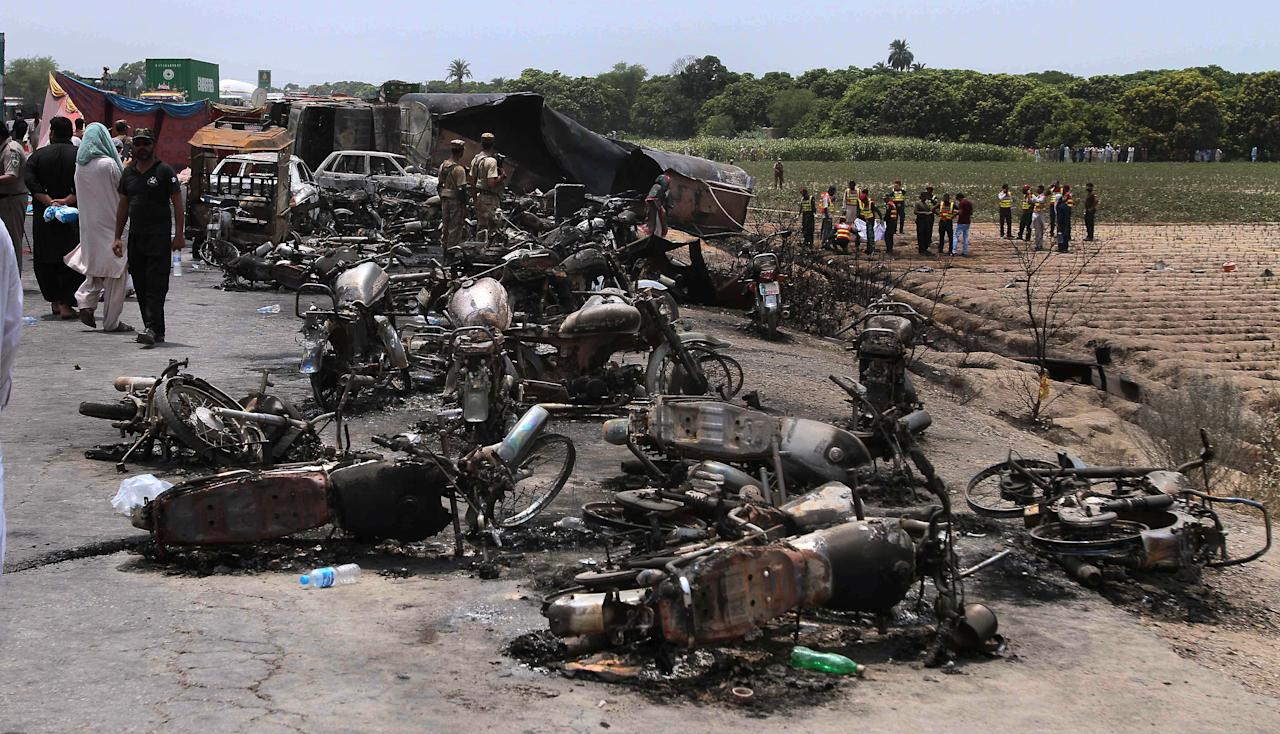 Pakistan army soldiers stands guard while rescue workers examine the site of an oil tanker explosion at a highway near Bahawalpur, Pakistan, Sunday, June 25, 2017. An overturned oil tanker burst into flames in Pakistan on Sunday, killing more than one hundred people who had rushed to the scene of the highway accident to gather leaking fuel, an official said. (AP Photo/Iram Asim)