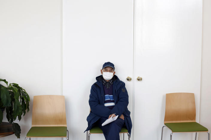 FILE - In this Jan. 18, 2021, file photo, a man waits prior to receiving the Pfizer-BioNTech COVID-19 vaccine at a center in Saint-Denis, north of Paris. Many people lining up for vaccines in the Paris suburb are particularly grateful for the injections. The surrounding region is the poorest in mainland France, with 130 languages spoken and the country's highest rise in mortality last spring. (AP Photo/Thibault Camus)
