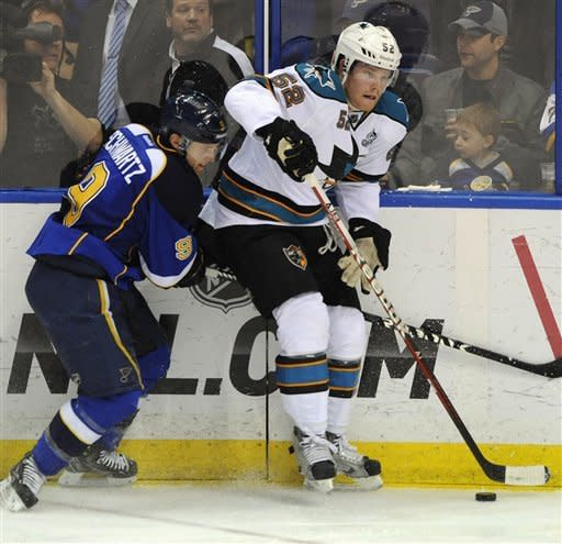 St. Louis Blues' Jaden Schwartz (9) and San Jose Sharks' Matt Irwin (52) battle for a loose puck in the second period of an NHL hockey game Tuesday, March 12, 2013, in St. Louis. (AP Photo/Bill Boyce)
