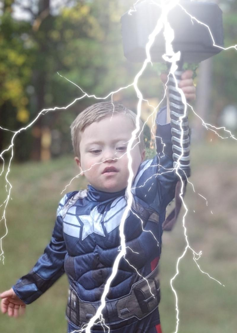 Adam's son dressed as Captain America holding Thor's hammer with lightning bolt effect..