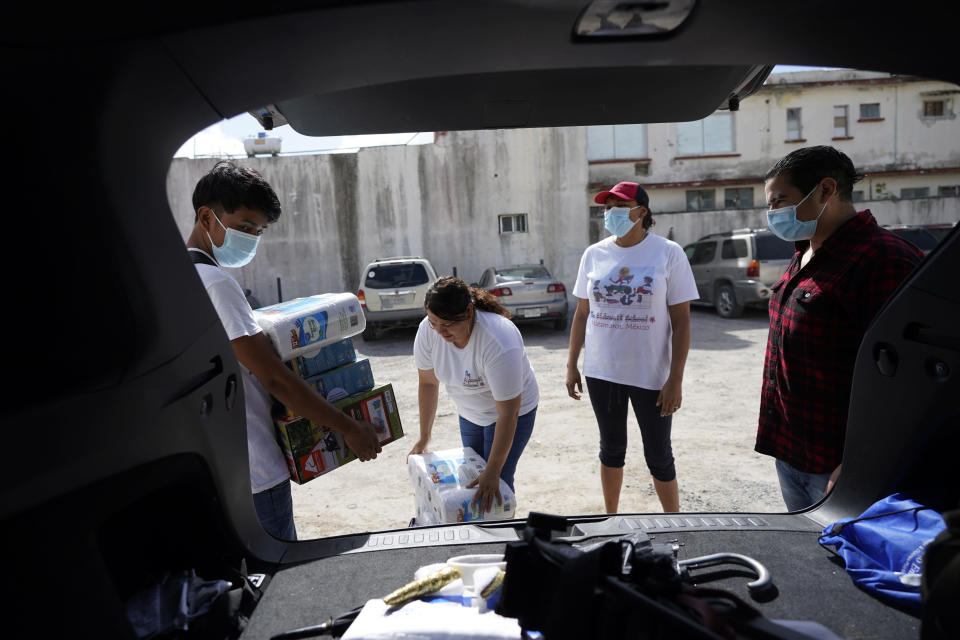 Sidewalk School founder Felicia Rangel-Samponaro, second from right, works works with staff to gather supplies, on Friday, Nov. 20, 2020, in Matamoros, Mexico. Like countless schools, the Sidewalk School went to virtual learning amid the coronavirus pandemic, but instead of being hampered by the change, it has blossomed. (AP Photo/Eric Gay)