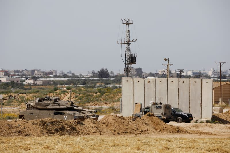 FILE PHOTO: An Israeli tank and a military vehicle can be seen next to a security barrier near the border between Israel and the Gaza Strip